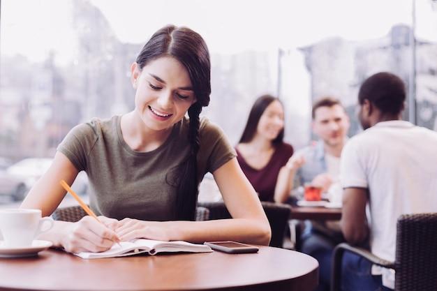 Красивая приятная студентка замечает свои идеи, глядя вниз и улыбаясь