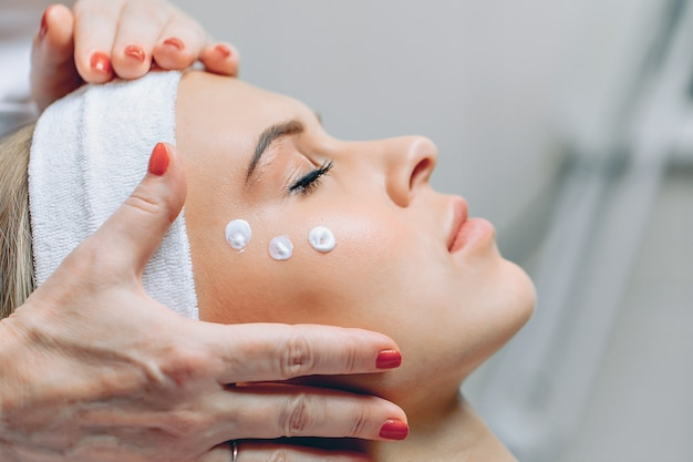 Красивая приятная девушка наслаждается косметическими процедурами, лежа с кремом, нанесенным на лицо, прежде чем нанести его на лицо.