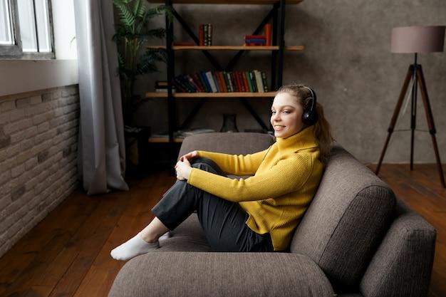 自宅のソファに座ってヘッドフォンで音楽を聴いて喜んでいる美しい女性。高品質の写真 Premium写真