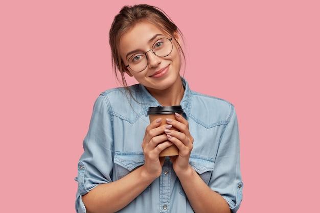 丸い透明なメガネで美しい喜んで若い白人女性は、ホットテイクアウトコーヒーを保持します