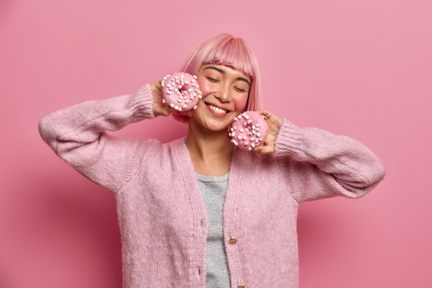 Beautiful pleased young woman smiles with closed eyes, holds delicious glazed donuts, imagines pleasant taste of sweet dessert, has dyed pink hair, wears warm sweater, has fun, poses indoor.