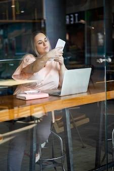 셀카를 찍는 아름다운 플러스 사이즈 비즈니스 여성은 카페에서 원격으로 일하는 스마트폰을 사용합니다.