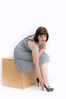 Beautiful plus-size girl in a dress sits on a wooden drawer and straightens her high-heeled shoes. isolated on white background