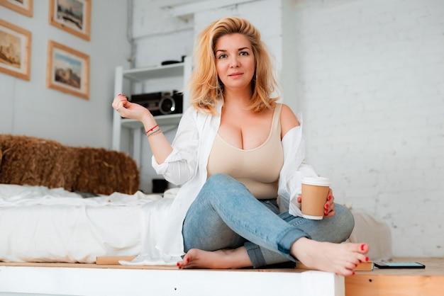 큰 가슴을 가진 아름다운 더하기 크기의 소녀는 커피와 함께 흰색 바닥에 앉아 있습니다. 신체 양성, 다이어트, 매력적인 몸매, 섹시, 금발 30 세, 패션, 열성, 배려.