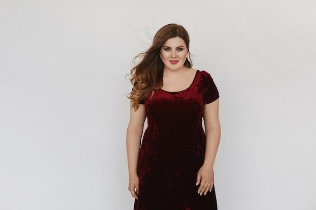 白で分離されたモダンな赤いベルベットのドレスで美しいプラスサイズのモデルの女の子。明るいメイクとスタジオでポーズをとってスタイリッシュな髪型と若い太った女性。 xxxlファッションの概念。