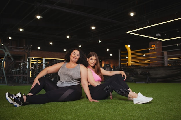 Beautiful plus size sportswomen exercising at the gym together