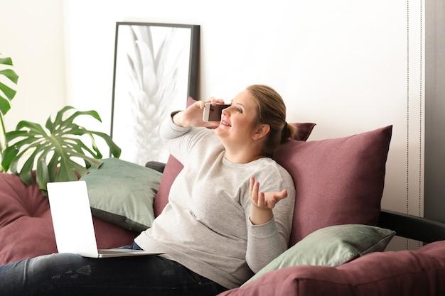 自宅で携帯電話で話している美しいプラスサイズの女性。ボディポジティブの概念