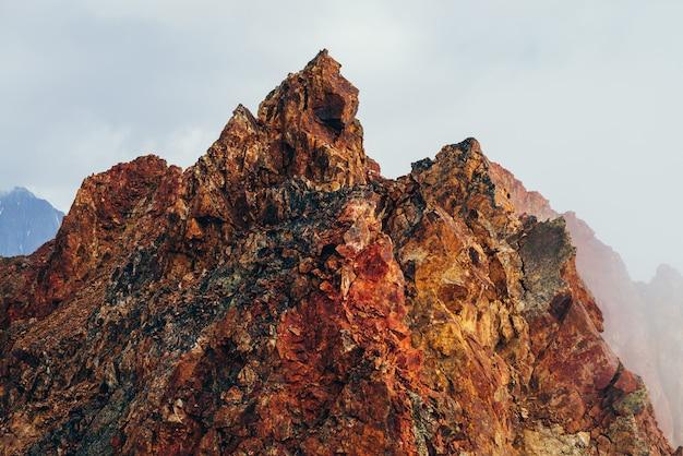 Красивая остроконечная скалистая вершина в облачном небе. яркий большой заостренный скалистый пик. гигантский кусок камня. атмосферный минималистский альпийский пейзаж. острые скалистые горы в небе. прекрасные горные пейзажи.
