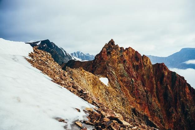Красивая остроконечная скалистая вершина на гигантской снежной горе. яркий большой заостренный скалистый пик. атмосферный минималистский альпийский пейзаж. острые скалистые горы в облачное небо. прекрасные горные пейзажи.