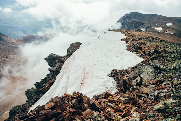 Beautiful pointy cliff on high rocky mountain edge with snow among thick low clouds