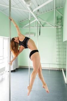다른 포즈에서 장대 댄스를 수행하는 아름다운 폴 댄서