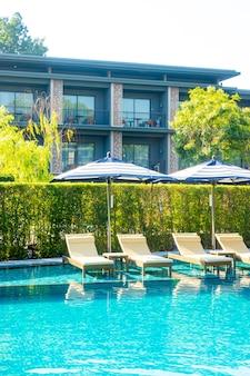 여행 및 휴가 개념에 대한 호텔 리조트 수영장 주변의 아름다운 수영장 의자 침대와 우산