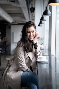 Beautiful portrait asian girl sitting on counter bar in coffee shop putting hand on her chin looking at camera with smile.