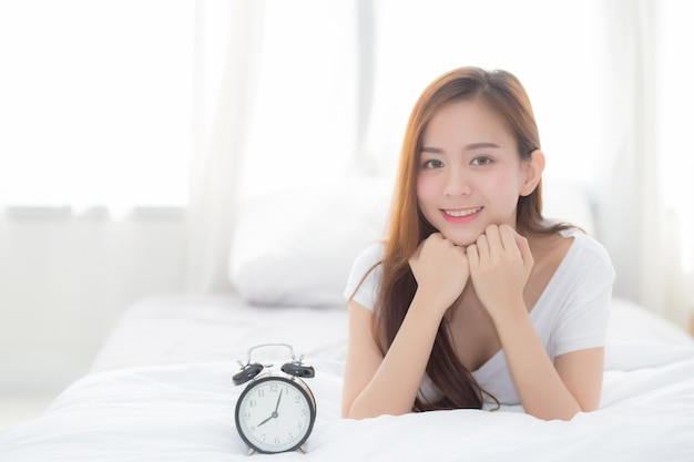 Beautiful of portrait asian woman wake up in morning and alarm clock