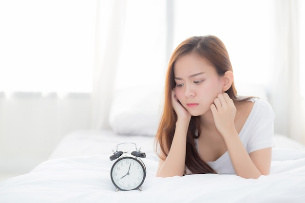 Beautiful of portrait asian woman wake up in morning annoyed looking  alarm clock