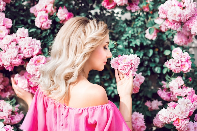 Beautiful portrait of a blonde woman in pink roses. close-up, makeup, extended eyelashes