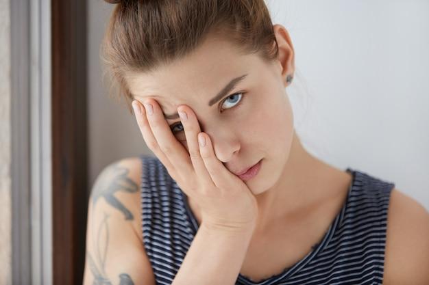 Bellissimo ritratto di donna annoiata che riposa metà del suo viso sul palmo della mano. attraente ragazza con i capelli castani e gli occhi azzurri che si stanca di conversazioni traballanti, cercando di nascondersi da discorsi noiosi sotto il braccio.