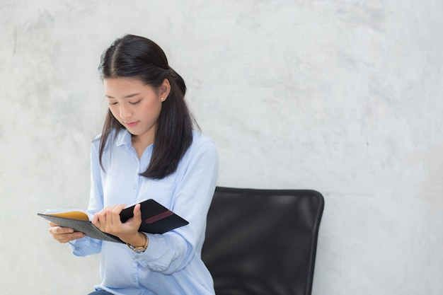 Beautiful of portrait business asian young woman reading on notebook