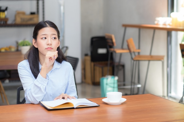 Beautiful of portrait business asian young woman thinking idea and writing on notebook.