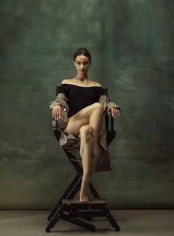 Beautiful portrait. graceful classic ballerina dancing, posing isolated on dark studio background. stylish trench coat. grace, movement, action and motion concept. looks weightless, flexible.
