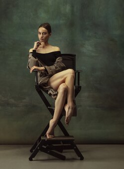 Красивый портрет. изящные классические танцы балерины, позирует, изолированные на темном фоне студии. стильный тренч. изящество, движение, действие и концепция движения. выглядит невесомо, гибко.