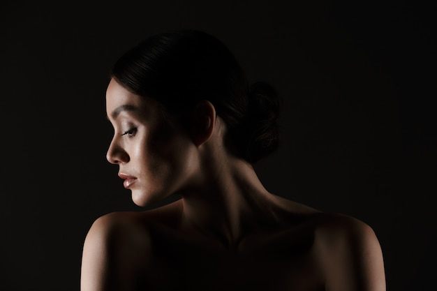 Beautiful portrait of half-naked elegant woman with dark hair in bun putting head aside, isolated over black