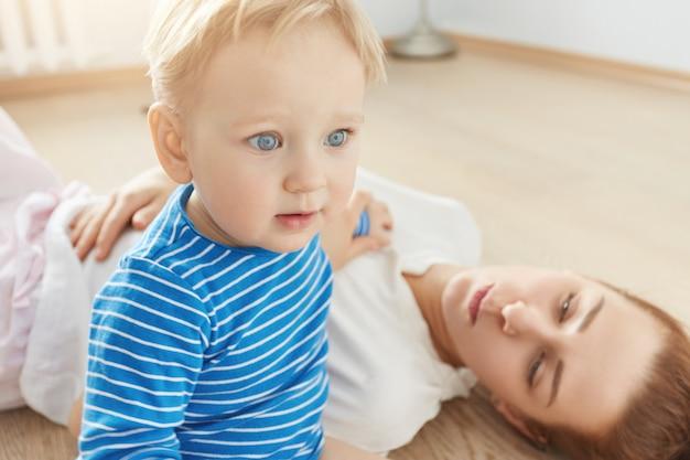 Bellissimo ritratto del ragazzino biondo con gli occhi azzurri e madre premurosa sdraiato sul pavimento a casa. piccolo bambino in vestiti blu che guarda avanti. la sua attraente mamma attenta che lo guarda con amore.