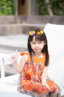 プールで笑って座っている美しい肖像画の少女のアジア人