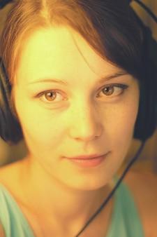 헤드폰 근접 촬영에 여자의 아름 다운 초상화