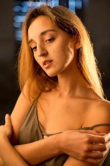 木製の背景に女の子の美しい肖像画。ストラップの軽いドレスを着た女の子