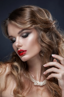 어린 소녀, 빨간 립스틱과 전문 메이크업의 아름 다운 초상화. 진주로 만든 목 보석에 어두운 배경에 쐈어. 깨끗한 피부, 아름다움.