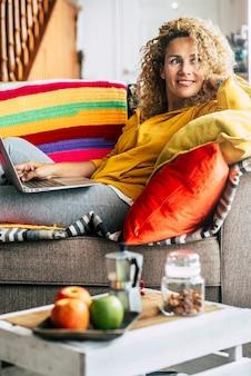 Красивый портрет взрослой молодой женщины дома за завтраком и с помощью портативного компьютера