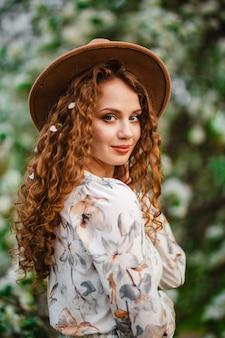그녀의 곱슬 머리에 사과 나무의 꽃과 매력적인 젊은 여자의 아름 다운 초상화. 여성 봄 공원에서 베이지 색 모자와 흰색 드레스를 입고. 새로운 시즌 개념.
