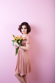 Красивый портрет красивой женщины с букетом цветов на розовом фоне.
