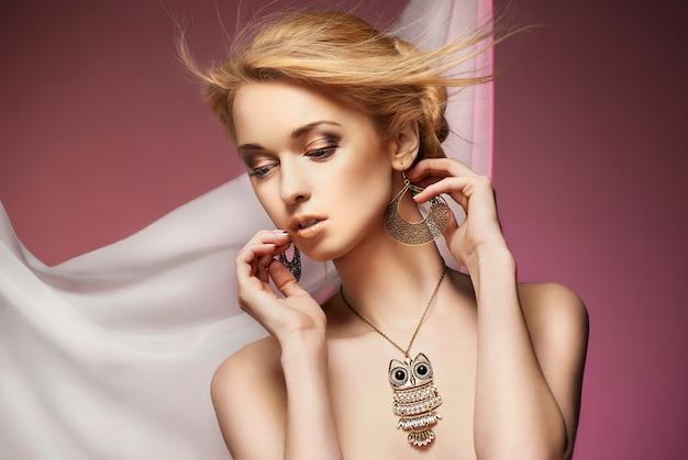 귀중 한 목걸이와 귀걸이 근접 촬영으로 섹시 한 젊은 거만 여자의 아름 다운 초상화. 스튜디오 촬영