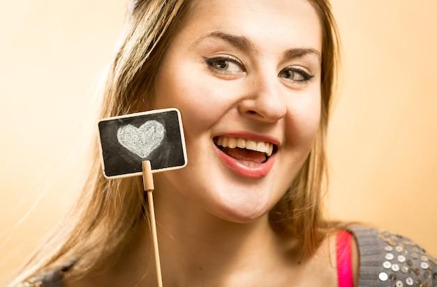 Красивый портрет улыбающейся женщины, позирующей с декоративным меловым кабаном с нарисованным сердцем