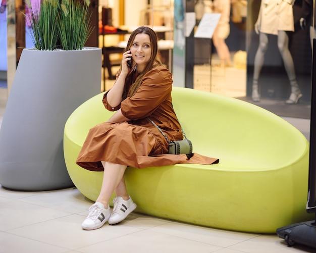 ショッピングセンターのファッションブティックの窓を背景に女性の美しい肖像画