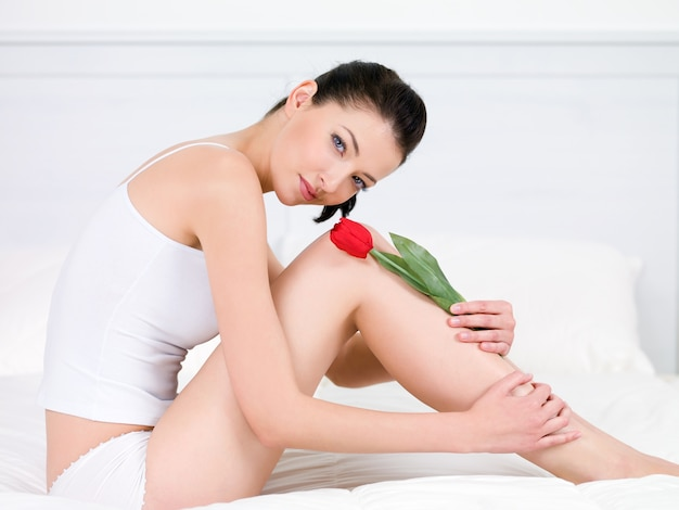 Beautiful portrait of smiling young pretty woman with red tulip on legs - indoors