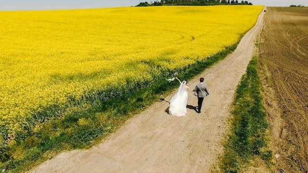 The beautiful portrait wedding couple is walking near the field top view
