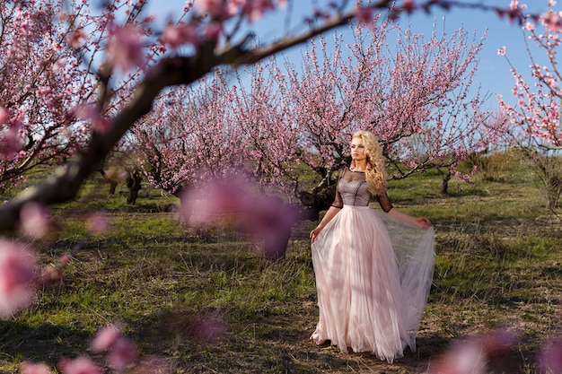 Beautiful portrait of a woman in a garden of flowering peaches