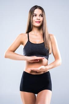 아름 다운 초상화 여자 손 제스처 심장 모양의 뱃속에 여자 운동에 고립 된 화이트 스포츠 의류를 입고.