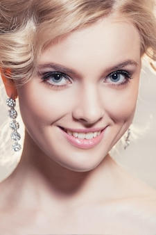 Beautiful portrait of a woman with blonde hair with an evening make-up .