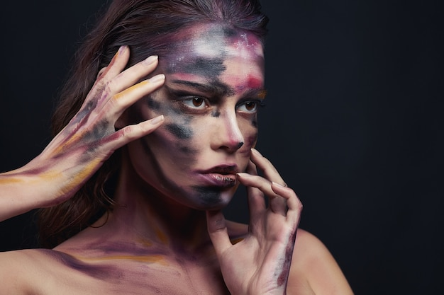 Beautiful portrait of woman with drawing paint on the face and body