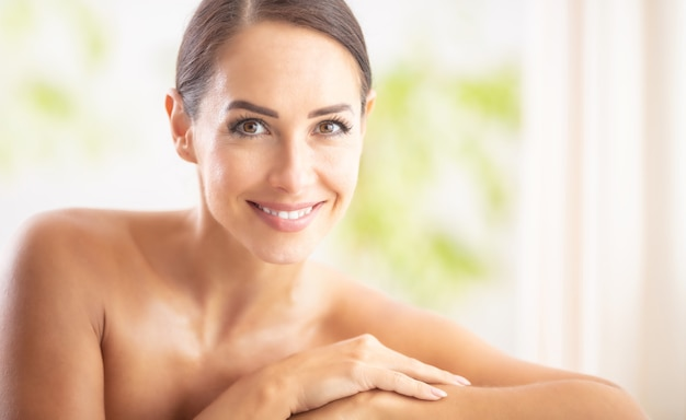 Beautiful portrait of young adult woman with clean skin without make-up sitting in a beauty salon and looking into the camera. spa skincare wellness and cosmetics concept.