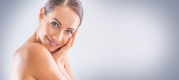 Beautiful portrait of young adult woman with clean skin without make-up. spa skincare wellness and cosmetics concept. blue gray panoramic banner.