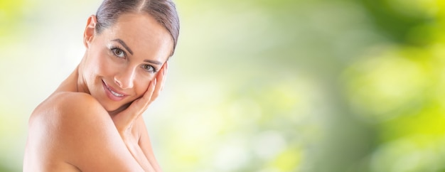 Beautiful portrait of young adult woman with clean skin without make-up. spa skincare wellness and cosmetics concept. blurred green panoramic banner.