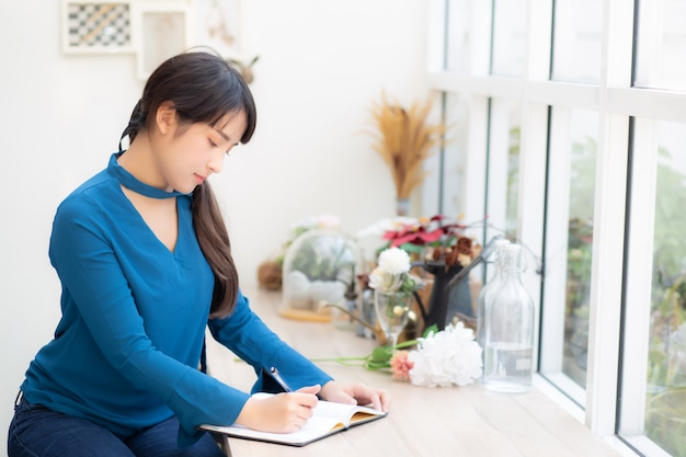 Beautiful portrait young asia woman writer writing on notebook or diary with happy