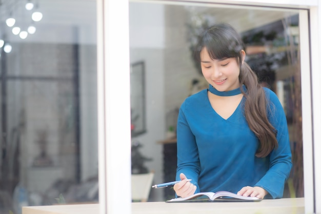 Beautiful portrait young asia woman writer writing on notebook