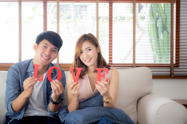 Beautiful portrait young asian couple sitting on sofa