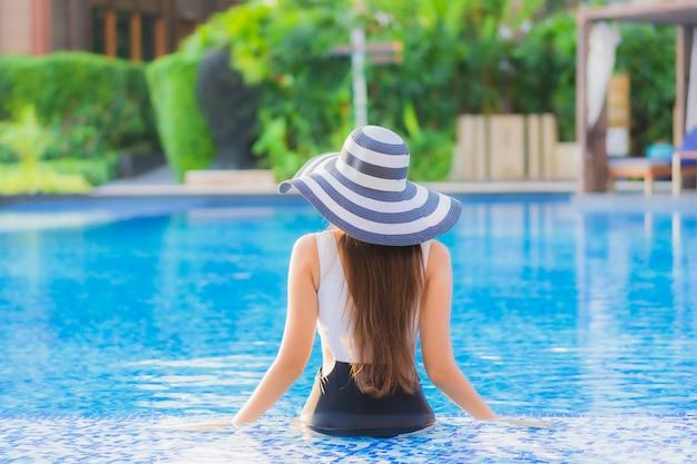 Улыбка красивой азиатской женщины портрета счастливая ослабляет вокруг бассейна в курортном отеле